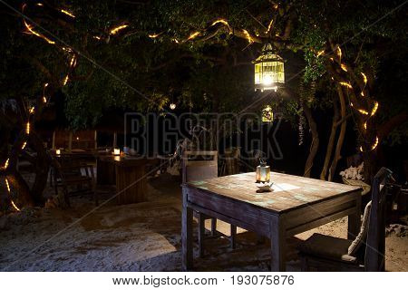 Romantic dinner on the beach in cafes under the open sky under a tree with a lantern