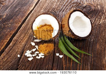 Coconut sugar. Fresh healthy coconut halfs on wooden table with leaves.