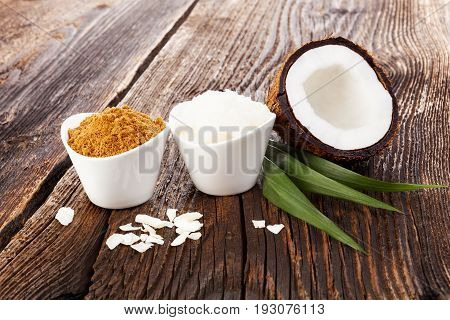 Coconut sugar and coconut oil and shredded coconut with leaf on wooden table. Healthy coconut products.