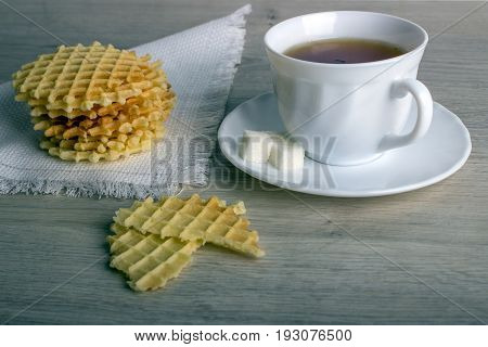 Breakfast With White Cup Of Black Tea With Waffles Stack On Napkin And Pieces Of Waffle On Wooden Su