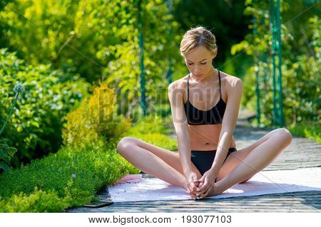 Fit woman sitting in the garden on a sunny day. Fitness training outdoors. Fitness classes outdoors. Attractive fitness woman. Workout outdoors. Healthy lifestyle