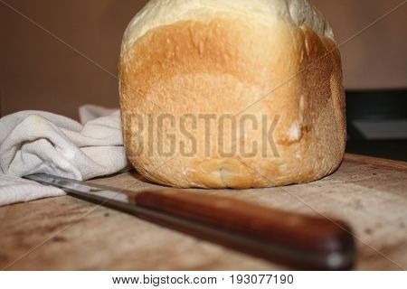 A loaf of home made bread on a cutting board with a bread knife.