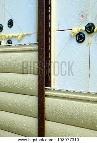 Siding panels mounting over insulation on building wall in rainy day closeup view