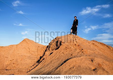 girl standing on a sand hill in black clothes