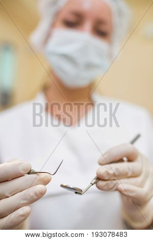 Female dentist with dental instruments closeup, selective focus
