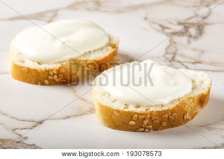 Sesame bagel with cream cheese on table