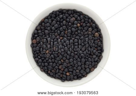 Beluga lentil seeds in white bowl, black lentils, from above, isolated on white background