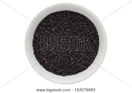 Black sesame seeds in white bowl, oilseed, from above, isolated on white background