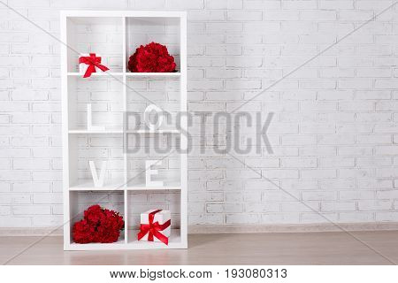 Valentine's Day Concept - Modern Wooden Shelf With Flowers And Gifts Over White Brick Wall