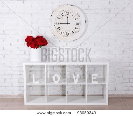 Wooden Letters Forming Word Love In Modern Shelf, Flowers And Vintage Clock Over Brick Wall
