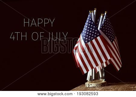some american flags in a glass jar, on a rustic wooden surface and the text happy 4th of july on a black background