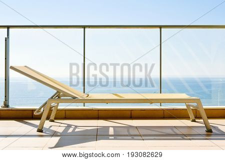 closeup of a sun lounger in a balcony, with the ocean in the background