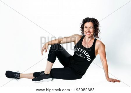 A muscular female weight trainer leans on her arm while posing for the camera on a white background. She has a big smile and curly black hair.