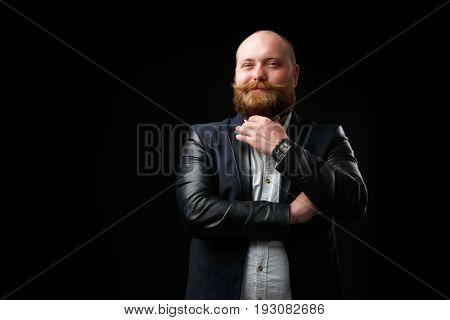 Pleased man stroking ginger beard