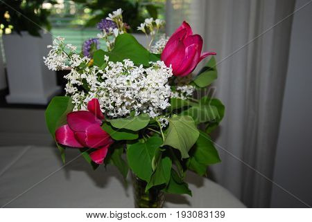 Bouquet with colorful summer flowers in a vase on a table indoors