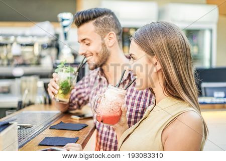 Young cheerful couple toasting cocktails in miami lounge disco bar - Young people having fun with new mixology club alcohol beverage - Party and happy hour concept - Focus on woman mouth - Warm filter