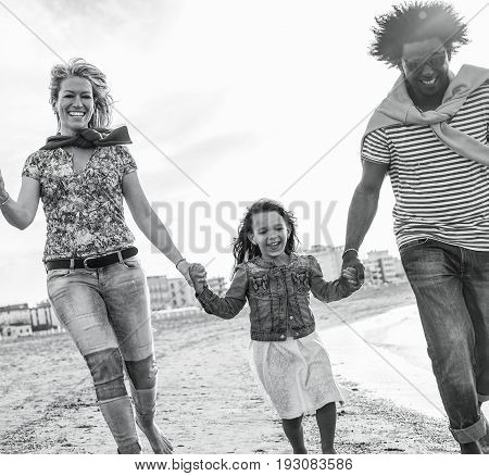 Mixed race family friends running on the beach - Diverse culture parents and child playing together - New multi ethnic families and travel concept - Main focus on left woman - Black and white editing