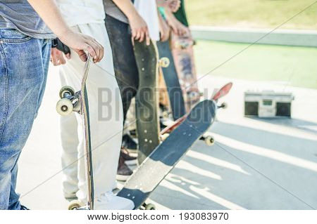Group of skaters friends in urban contest with skateboards in their hands - Young men training with boards in skate park - Extreme sport concept - Focus on right man's hand board - Warm filter