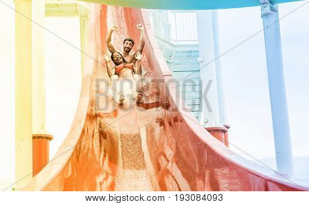 Young couple splashing into a waterslide at aqua park for summer vacation - Multiracial people having fun outdoor - Travel and love concept - Focus on them - Radial blue and yellow filters editing