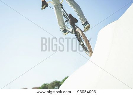 Bmx biker jumping in city skate park outdoor - Young trendy man performing skills and tricks with special bicycle - Extreme sport concept - Focus on bottom wheel - Warm contrast filter
