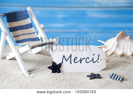 Summer Label With French Text Merci Menas Thank You. Blue Wooden Background. Card With Holiday Greetings. Beach Vacation Symbolized By Sand, Deck Chair And Shell.