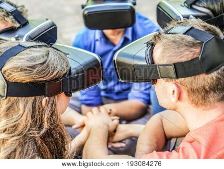 Young friends wearing virtual reality glasses outdoor - University students having fun with new technology vr headset goggles - Focus on right man headset - New generation mania trends - Warm filter