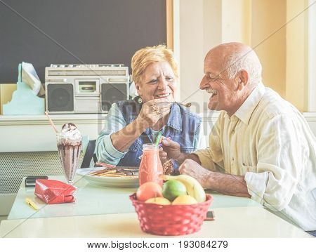 Happy senior couple having fun eating pancakes during united states vacation - Mature people enjoying brunch at bar restaurant - Active elderly and travel concept - Focus on man face - Vintage filter