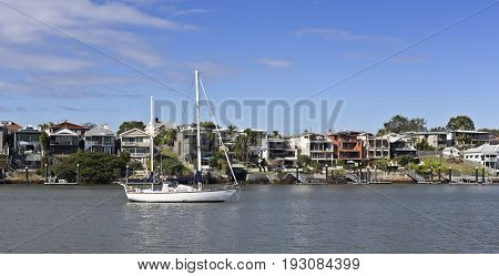 BRISBANE, AUSTRALIA - June 22, 2017: Two masted sailing boat moored in the Brisbane River in front of the million dollars mansions of the Eastern suburb of Norman Park Brisbane Australia