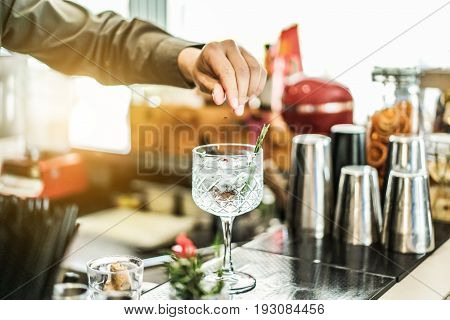 Bartender preparing cocktail with gin rosemary and pink pepper inside bar - Soft focus on top crystal glass - Lifestyle nightlife drinking and entertainment concept - Contrast retro filter