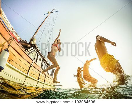 Young rich people diving from sailing boat into the sea - Crazy happy friends having fun in summer party day - Vacation friendship youth concept - Soft focus on left guys - Fisheye lens distortion