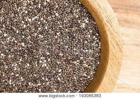 A pile of Chia Seeds in wood bowl on cutting board.
