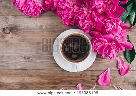 A cup of coffee pink peonies pattern on wooden background . Good morning. Women's or Mother's Day background.