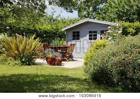 Shed with terrace and garden furniture in a garden