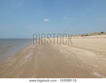 crosby beach near liverpool in summer with sand on a long beach and blue sky