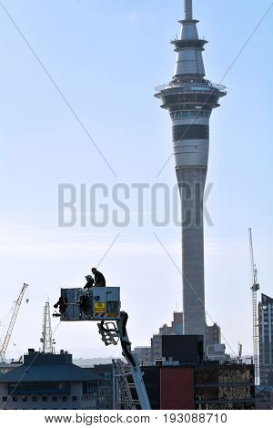 Firefighters On A Crane Platform Against Auckland Sky Tower