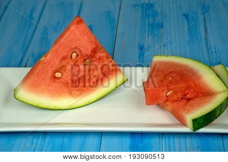 ripe triangle watermelon slices on white plate and blue painted wood