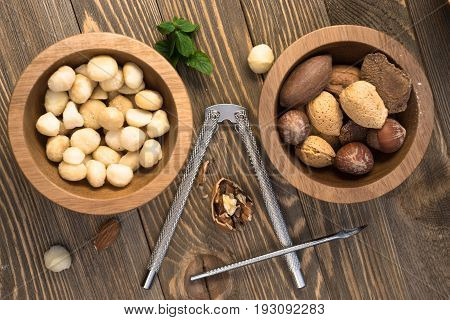 Utensils and nut filled bowls sit on wooden table