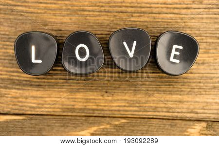 Black typewriter buttons laying on wood table say the word love