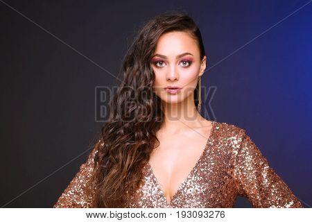 Beautiful young woman in evening dress on black background.