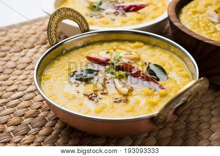 Indian popular food Dal fry or traditional Dal Tadka Curry served in 3 different bowls and placed together, closeup view over white background, selective focus
