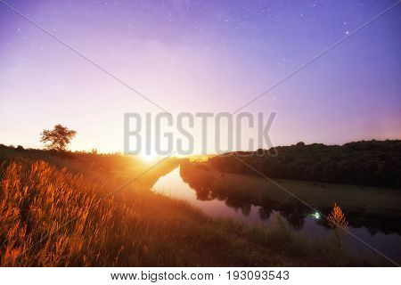 Beautiful dawn above the river and much of stars in the sky