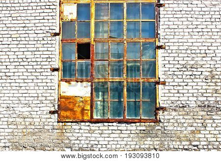 Old window with broken panes on the wall of an  old building