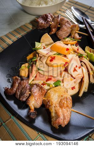 delicious spicy thai food of mix salad and hot dog Fried pork in back dish.