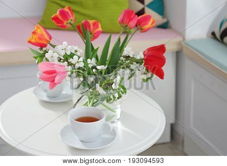 Vase with beautiful flowers and tea set on table in modern veranda interior