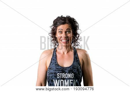 A muscular woman stands looking at the camera with clenched teeth and wide eyes with a surprised and excited expression. She is on a white background.