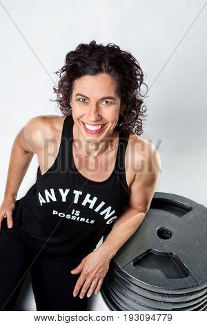 A smiling dark curly haired female weight lifter and trainer sits and leans on a pile of weight plates while posing for the camera on a white background.
