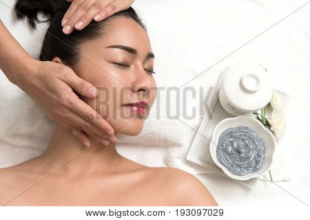 Close up of beautiful young asian woman lying with closed eyes and preparation face or head massage in spa or wellness Beauty healthy lifestyle and relaxation concept