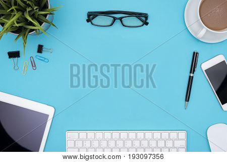 frame of office supplies computer pen pencil tablet phone flower eye glasses and coffee cup on blue desk table Top view with copy space