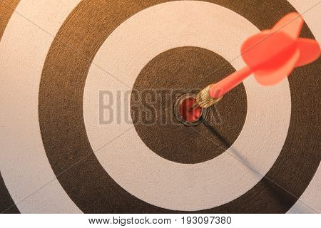 Red dart target arrow hitting on bullseye with sun light vintage style Target marketing and business success concept