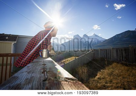 Young man standing at the patio and enjoying morning coffee with amazing view to high mountains - concept of inspiration, freedom, piece